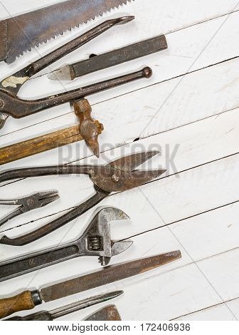 Many old rusty tools scattered on the wooden tstolu. View from above. Space for text.