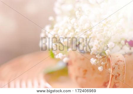Blurred abstract spring natural background with white flowers in a cup, copy space.