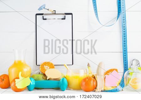 Fruit and juice orange apple banana dumbbell hand gripper and folder clipboard with blank paper sheet on white wooden background. Healthy lifestyle diet concept. Healthy eating for weight loss.