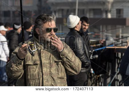 ISTANBUL TURKEY - DECEMBER 27 2015: Fisherman on Galata bridge smoking a cigarette before starting to fish