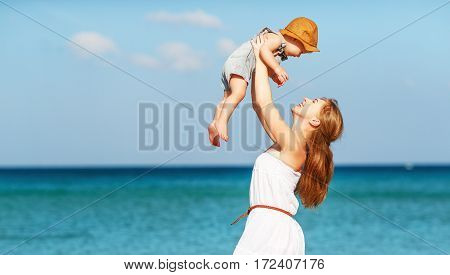 happy family mother with baby son walks by ocean on the beach in summer