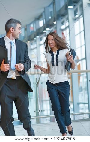 Happy businessman and businesswoman running