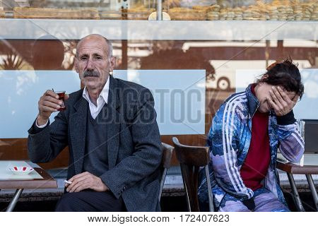 ISTANBUL TURKEY - DECEMBER 28 2015: Old Man drinking tea on a terrace of a cafe on the Asian side of the city