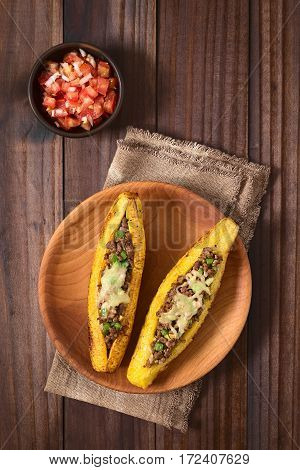 Baked ripe plantain stuffed with mincemeat olive green bell pepper and onion sprinkled with cheese a traditional dish in Central America called Canoa de Platano (Plantain Canoe) served with tomato and onion salad photographed overhead on dark wood with na