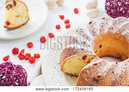 Bundt cake with raisins dried cherries and sugar powder on a white plate. Ring cake with icing sugar on white wooden table. Festive treat. Festive table setting.