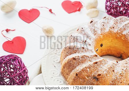 Bundt cake with raisins and sugar powder on a white plate. Ring cake with icing sugar on white wooden table. Festive treat. Festive table setting for Valentines Day