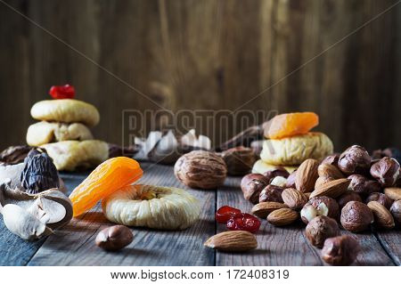 Mix of dried fruits and nuts almonds hazelnuts dried cherries dried apricots figs and prunes on rustic wooden background. Healthy and wholesome food. The concept of natural organic food diet.