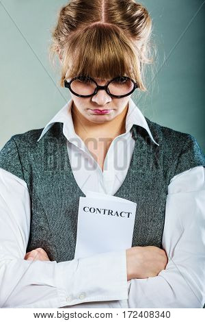 Business documents legal concept - closeup skeptical unhappy businesswoman holding contract in hands. Negative human emotion face expression feeling reaction