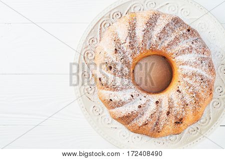 Bundt cake with cottage cheese raisins and sugar powder on a white plate with copy space. Homemade ring cake with icing sugar on white wooden table top view flat lay.