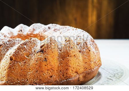 Bundt cake with cottage cheese raisins and sugar powder on a white plate with copy space. Homemade ring cake with icing sugar on wooden table closeup rustic style.