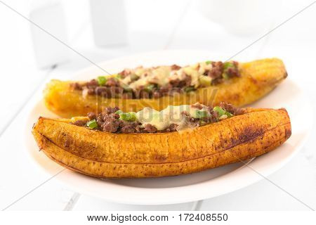 Baked ripe plantain stuffed with mincemeat olive green bell pepper and onion sprinkled with cheese a traditional dish in Central America called Canoa de Platano (Plantain Canoe) photographed with natural light (Selective Focus Focus on the middle front pa