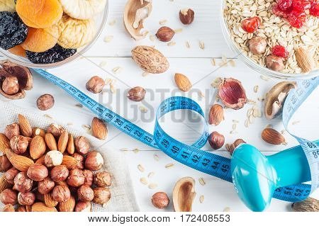 Healthy food. Ingredients for healthy breakfast on white wooden background with dumbbell and measuring tape. Oatmeal dried cherry apricots figs and nuts close up top view. The concept of natural organic food.