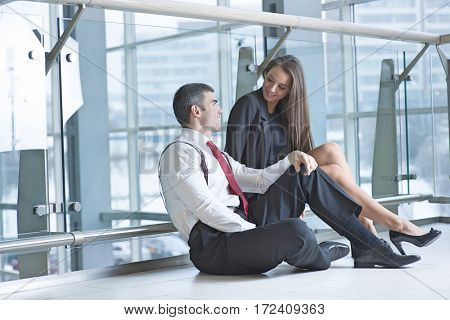 Businessman and businesswoman sitting on the ground talking