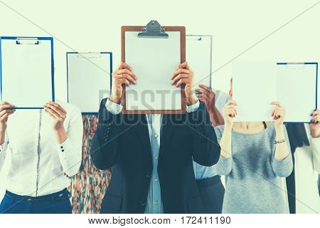 Team of businesspeople holding a folders near face isolated on white background .