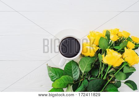 Cup of coffee with bouquet of yellow roses flat lay top view. Greeting card template. Floral background for mother's day wedding invitation greetings and invitation card.