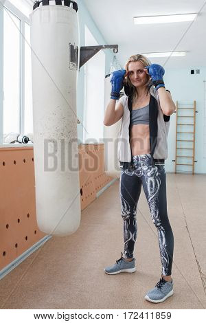 The Girl In A Sports Hall In Boxing Gloves Beats On A Pear