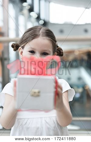 Young girl handing present towards camera