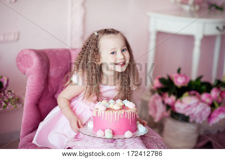 Happy kid girl 4-5 year old sitting in pink armchair with tasty cake in room. Looking at camera. Birthday party.