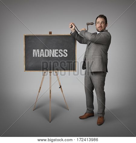 Madness text on blackboard with businessman drilling his head