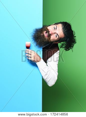 handsome bearded man with long beard and mustache has stylish hair on smiling face holding glass of alcoholic shot in vintage suede leather waistcoat on colorful studio background copy space