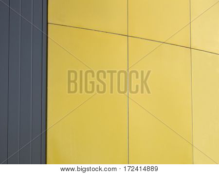 Lines and spaces in dark gray and bright yellow form a geometric abstract.