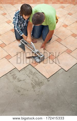 Young boy learning how to cut a ceramic floor tile - helped by his father top view