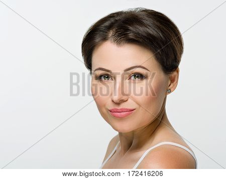 Portrait of beautiful girl with brown hair. Green eyes. Smiles.The picture was taken in a studio on a light background.