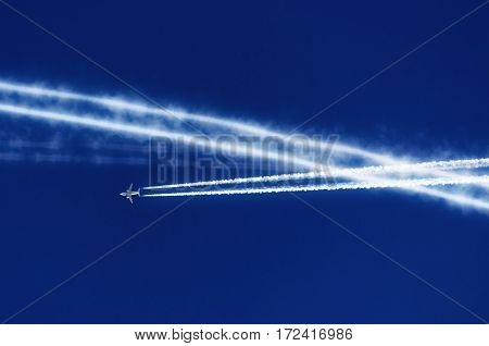 The blue sky and a lot of traces of the inversion contrail airplane