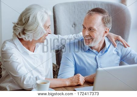 Eternal love. Cheerful delighted aged couple using laptop and talking while sitting in the cafe