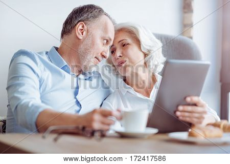 My dear. Pleasant delighted aged couple lookign at each other and expressing love while sitting in the cafe