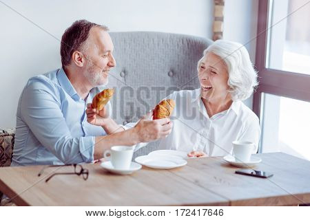 Involved in fun. Cheerful content aged couple eating croissants and sitting in the cafe while feeling delighted