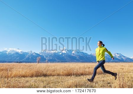 Happy Young Woman Runs On A Meadow At Sunset.