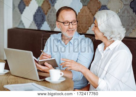 Busy days. Pleasant smiling aged couple sitting at the table and discussing project while conducting conversation