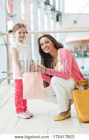 Mother giving daughter paper shopping bag