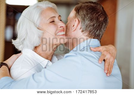 My love. Pleasant aged smiling couple embracing and expressing love