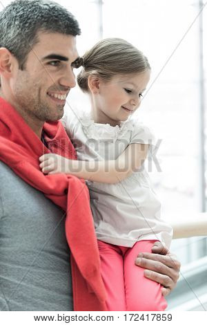 Father holding young daughter up at waist height