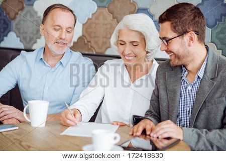 Put your signature. Cheerful delighted senior couple sititng at the table and signing the contract while meeting with insurance manager