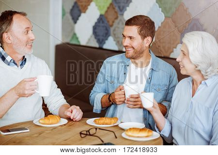 Family meeting. Positive smiling aged couple and their grandson sitting at the table and having lunch while resting in the cafe