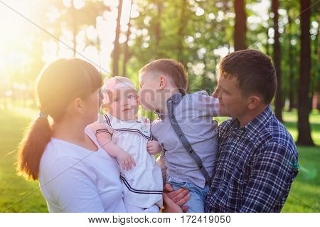 Young parents with children walk in the summer park.