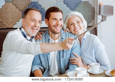 Enjoy the moment. Pleasant loving aged couple and their grandson sitting in the cafe and making selfies while having lunch