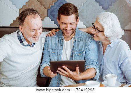 In the metwork. Positive delighted senior couple and their grandson sitting in the cafe and using tablet while resting together