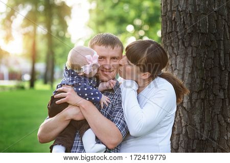 happy family in the park in spring sunny day kissing of daddy.