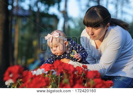 mother holds a baby daughter near the red flowers