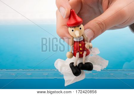 Hand Holding Pinocchio On In  Water