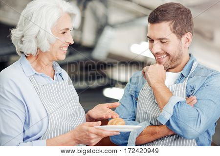 The best receipt. Pleasant aged woman holding plate with croissant and showing it to her grandson while standing in the cafe