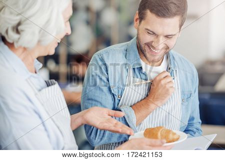 Just try it. Positive grandmother holding plate with croissant while cooking togethr with her grandson and putting down the receipt
