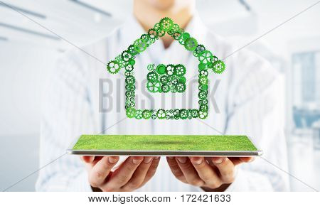 Close of businessman holding tablet pc with house sign made of connected gears. Mixed media