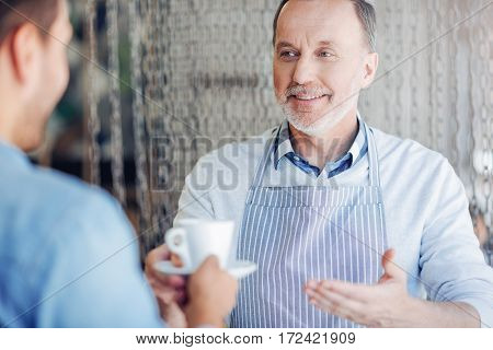Only best quality. Pleasant content smiling aged man holding cup of coffee and giving it to the guest while working in th cafe