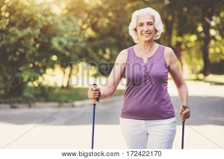 Outdoor activities. Happy delighted aged woman smiling and walking in the park while using poles