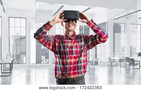 Young man with virtual reality headset or 3d glasses playing game in room